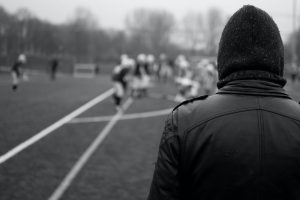 Hooded football hooligan faces away from the camera at a football team.