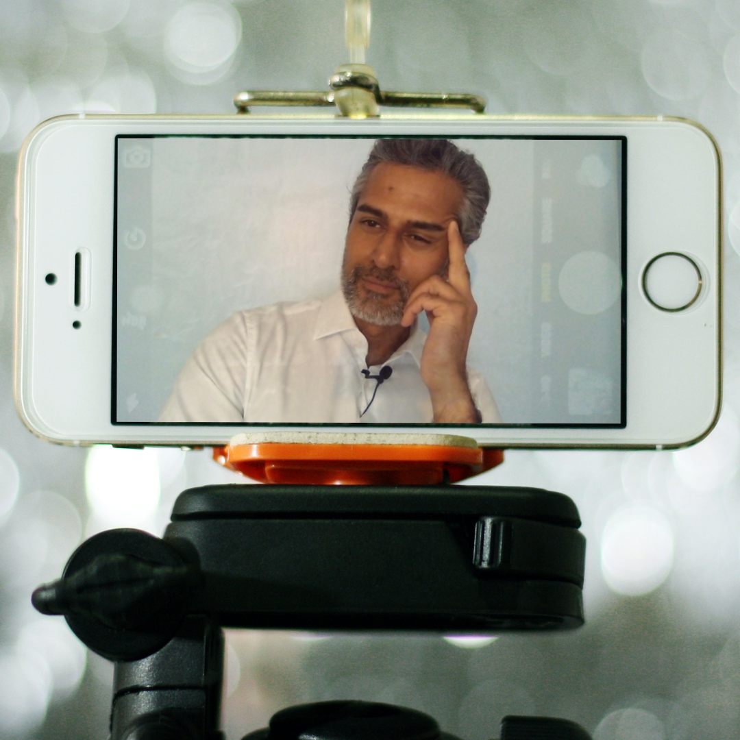 A tripod holding a phone on which is displayed Kal Sabir in a remote meeting.